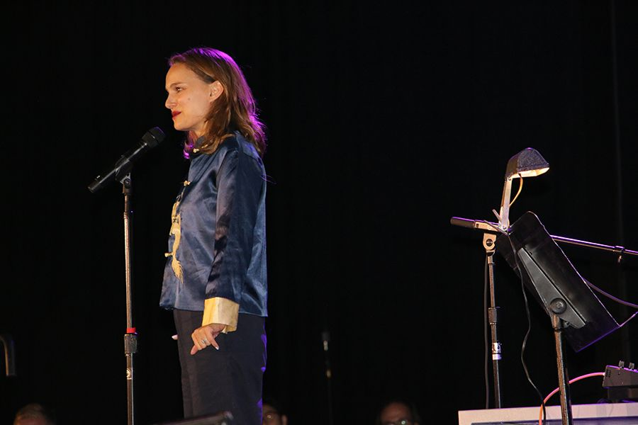 Natalie Portman stands at the microphone