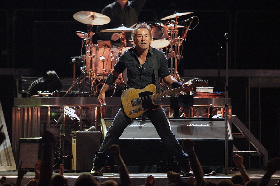 Bruce Springsteen holds a guitar on stage in front of a drummer