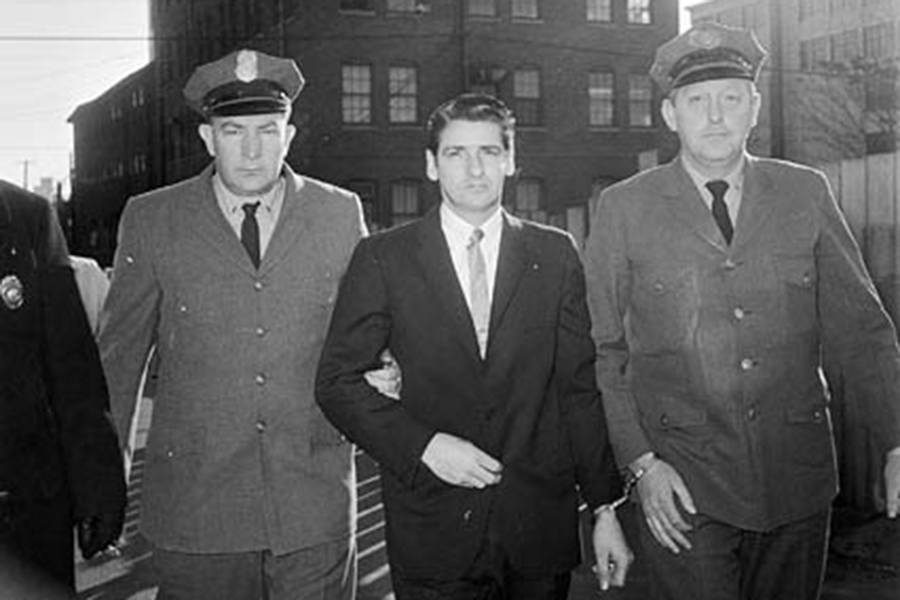 A man in a suit is flanked by two police officers