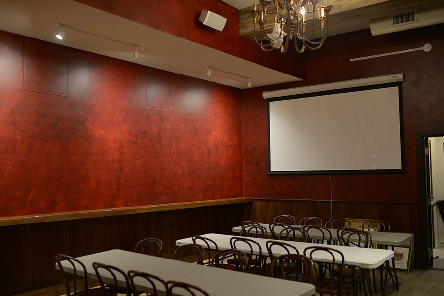 An overflow or private room with a projector screen at Democracy Brewing.