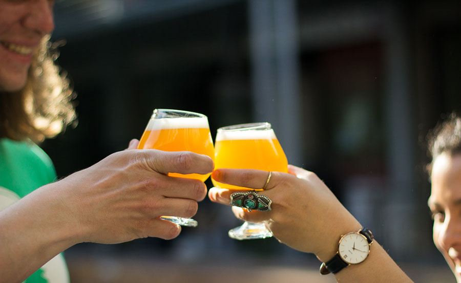 People saying cheers with Remnant brewing beers