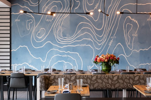 The far wall of the private dining room at Alcove is decorated with a bright blue topographical map