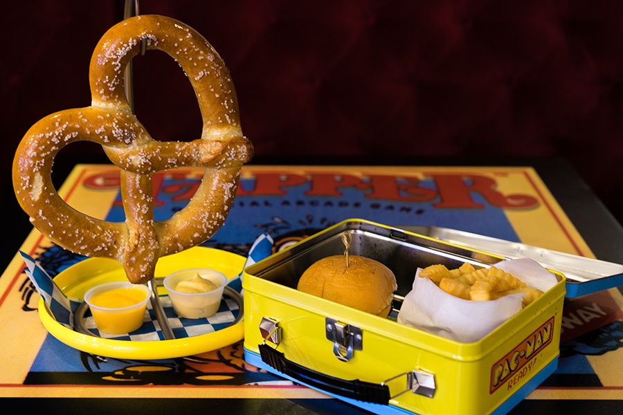 a soft pretzel and a hamburger and crinkle fries in a retro lunchbox at Versus in Boston
