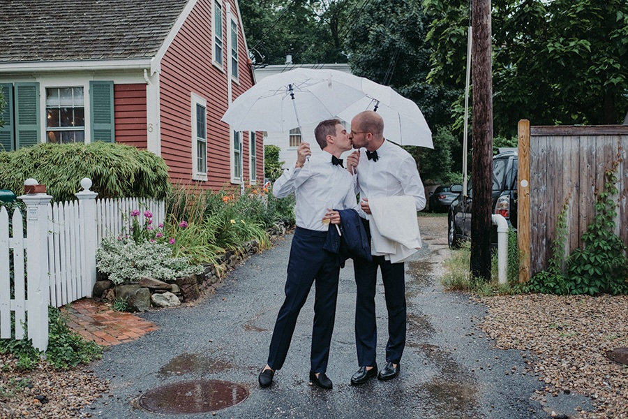 couple kisses under an umbrella