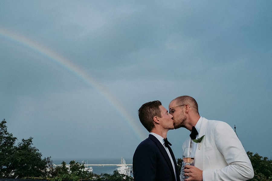 couple kisses under a rainbow at Provincetown wedding