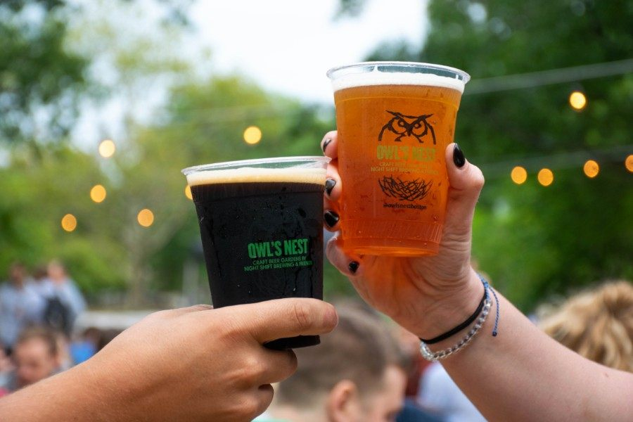 "Two plastic pints of beer ""cheers"" at Night Shift Owl's Nest beer garden"
