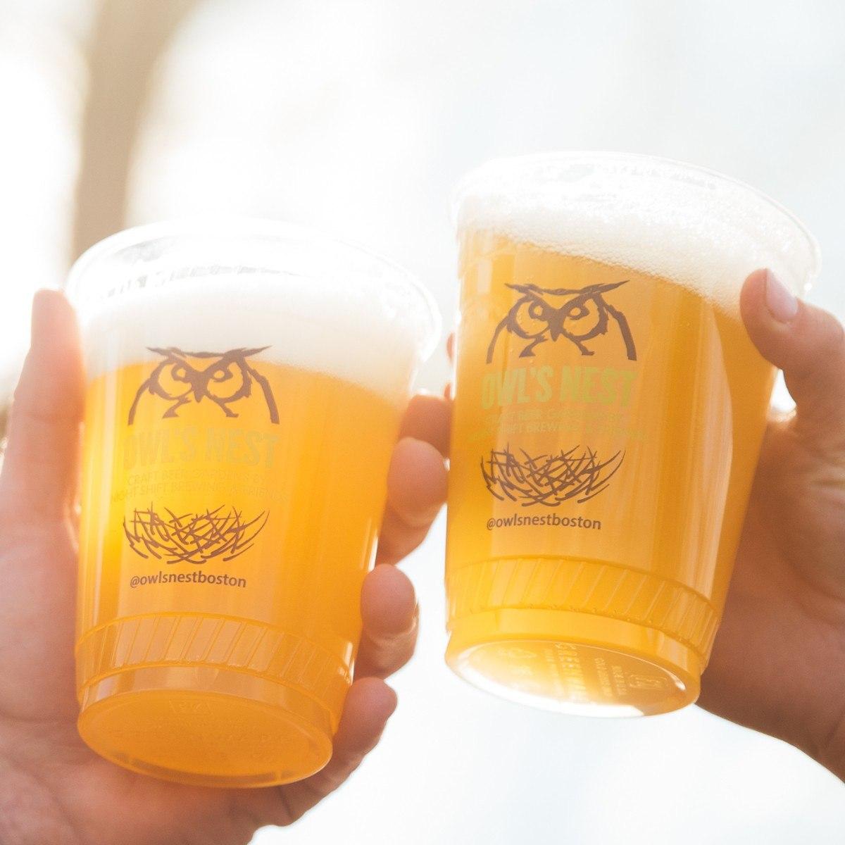 """Two plastic pints of beer """"cheers"""" at Night Shift Owl's Nest beer garden"""