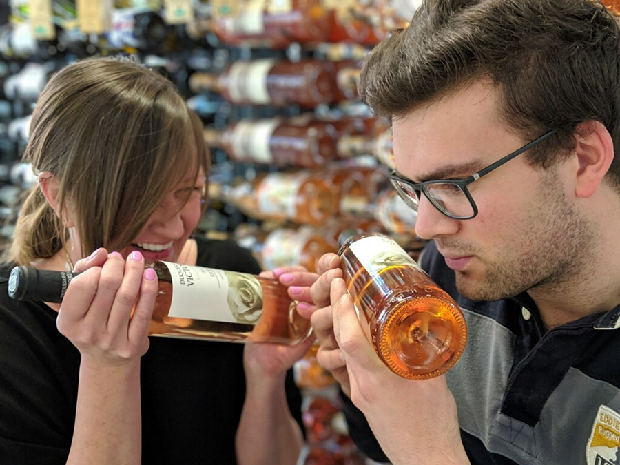 """Social Wines director of operations and wine Eileen Elliot and assistant wine buyer Alex Malecki checking out a """"scratch-and-sniff"""" wine label at Social Wines in Southie"""