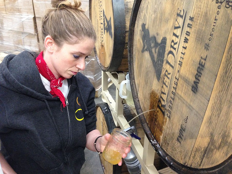 Lead CBC production brewer Lee Lord draws a barrel sample at Mystic.