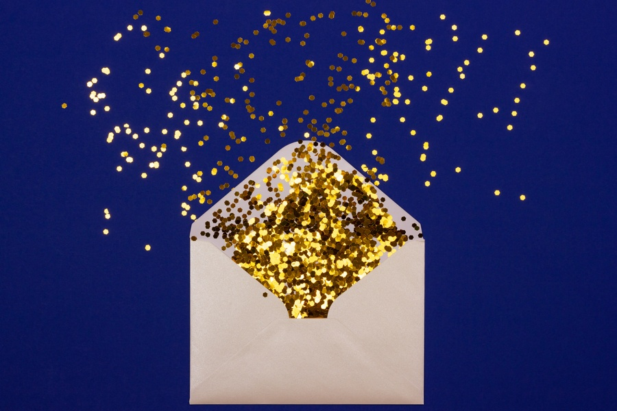 Golden confetti pouring out of white envelope on blue background. View from above.