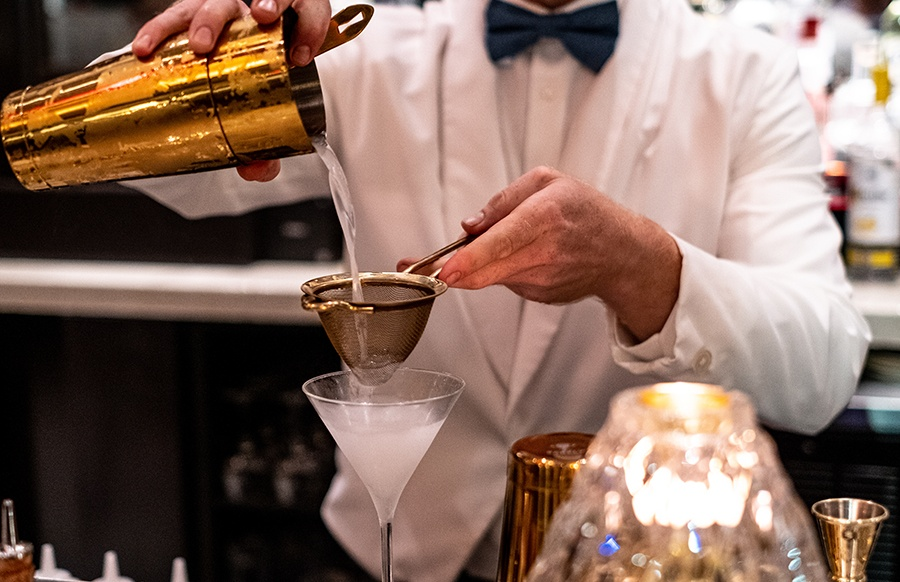 A bartender strains an ice-col gin martini at Orfano