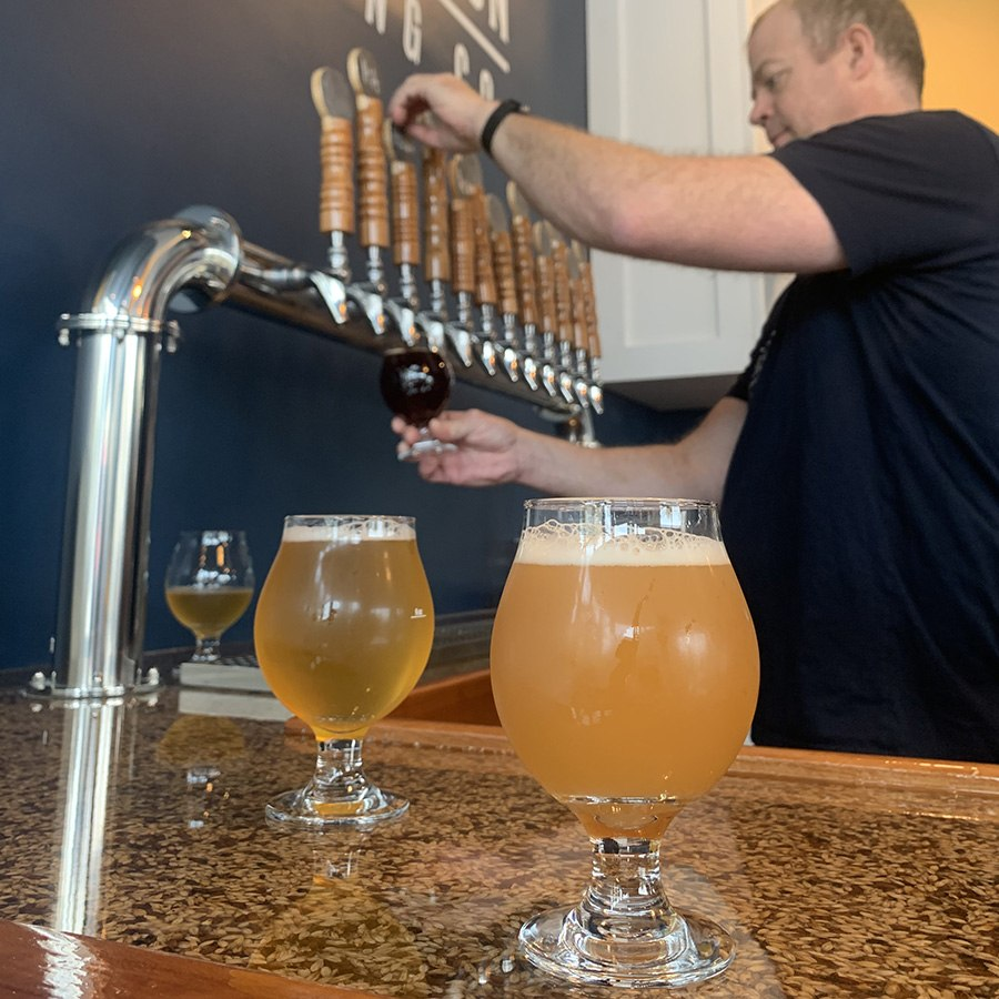 Brewer Mike Estey pours a beer at Distraction Brewing Co. during opening weekend, on Sunday, Oct. 20.