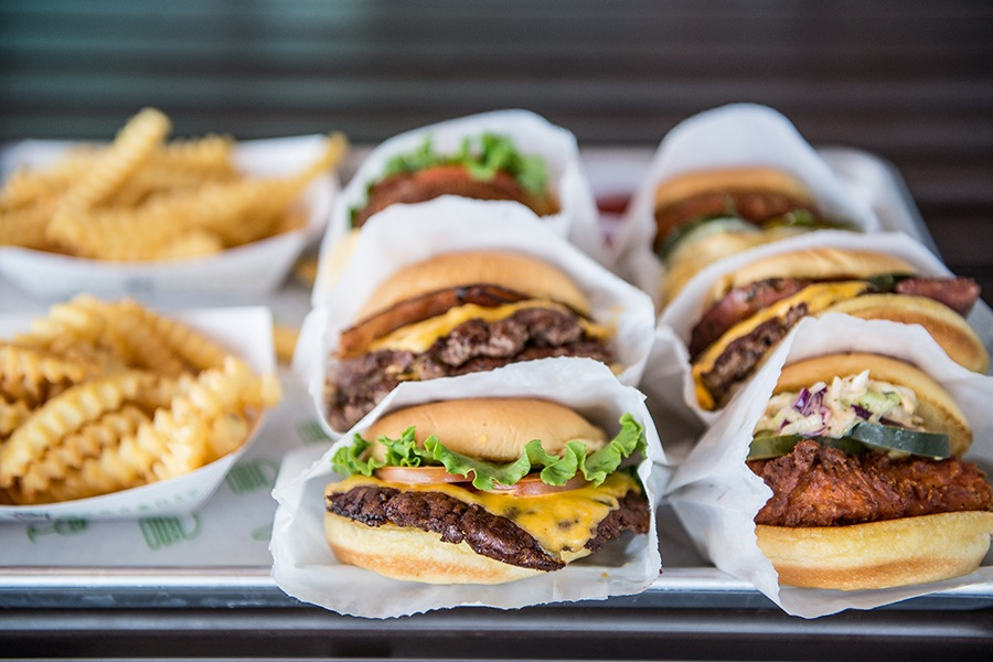 A tray of crinkle fries, burgers, and chicken sandwiches at Shake Shack