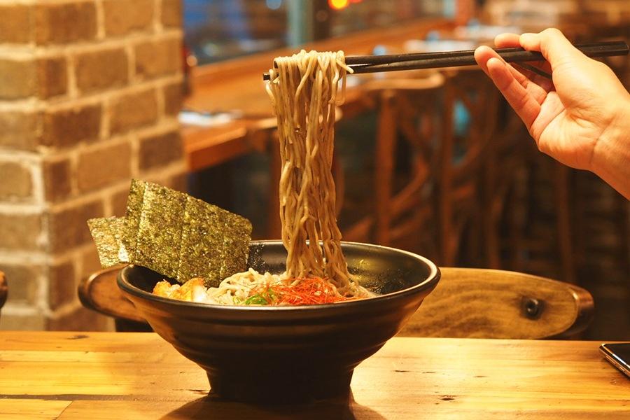 A person lifts ramen noodles with chopsticks from a bowl of black tonkotsu ramen at Soup Shack Brookline