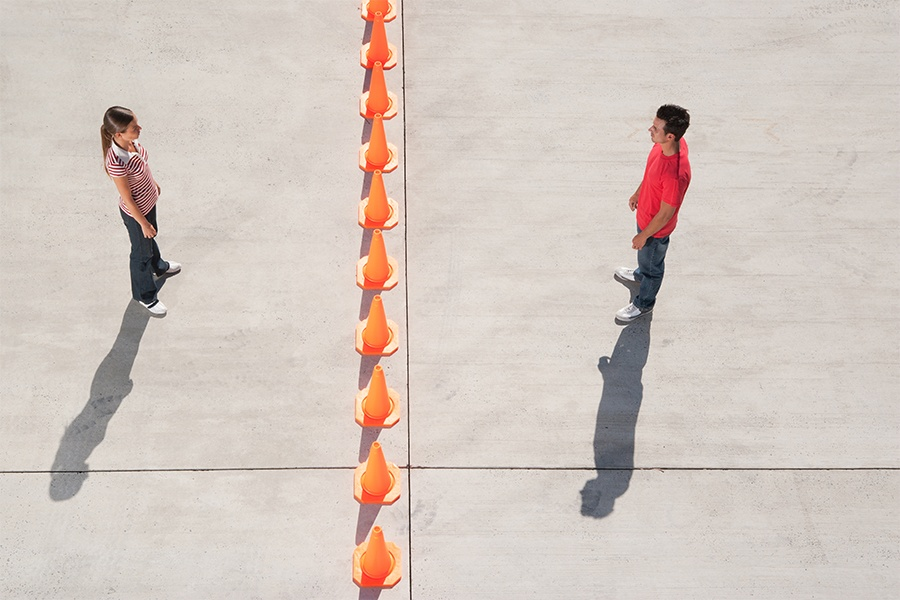 man and woman standing on either side of cones
