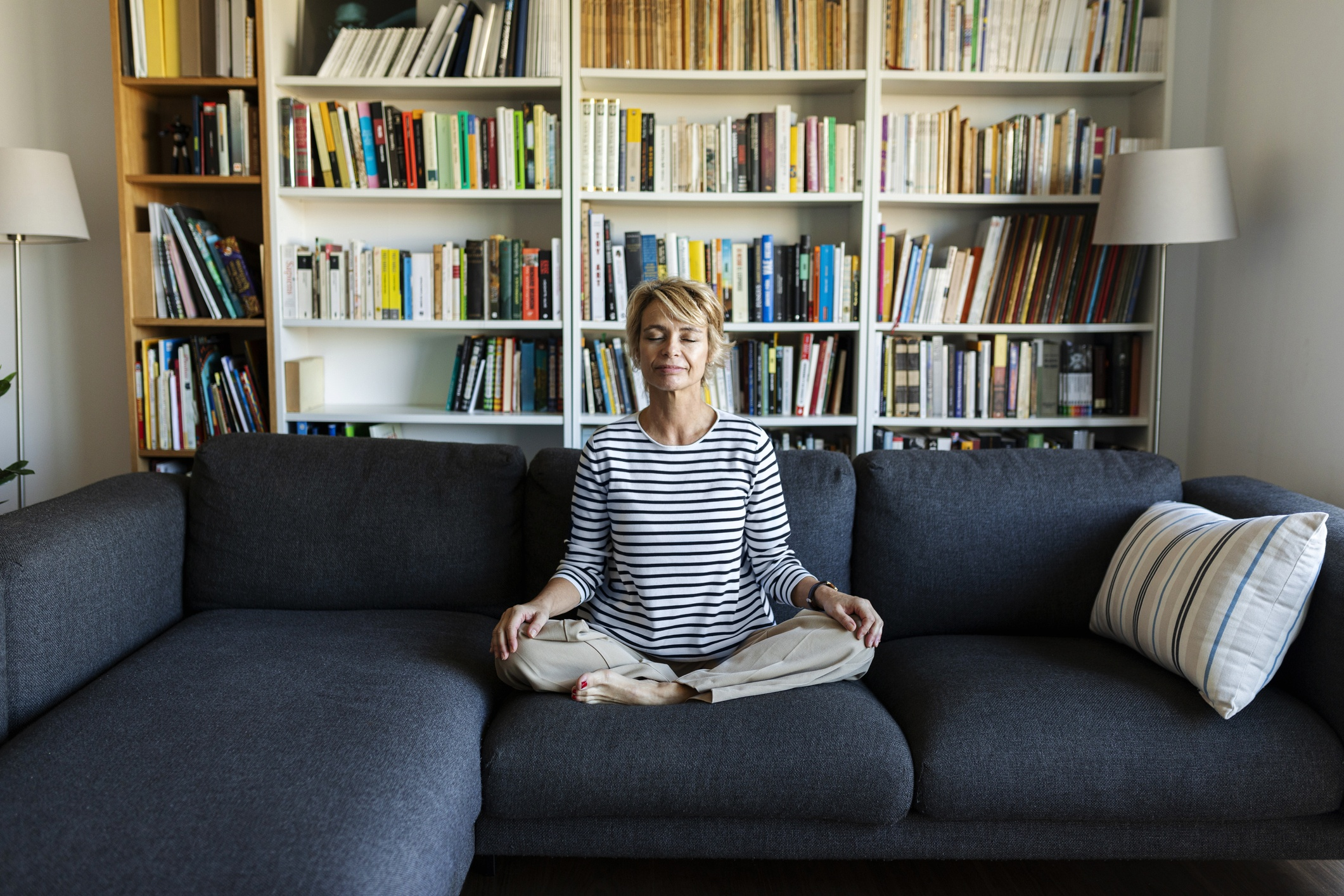 Mature woman practicing yoga on couch at home