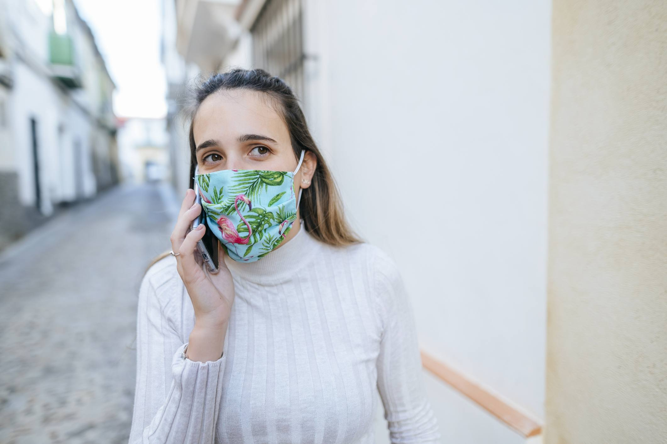 Woman with protective mask talking on the phone