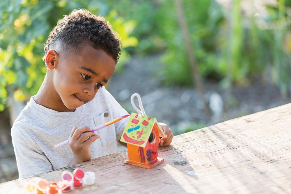 Little boy painting bird house