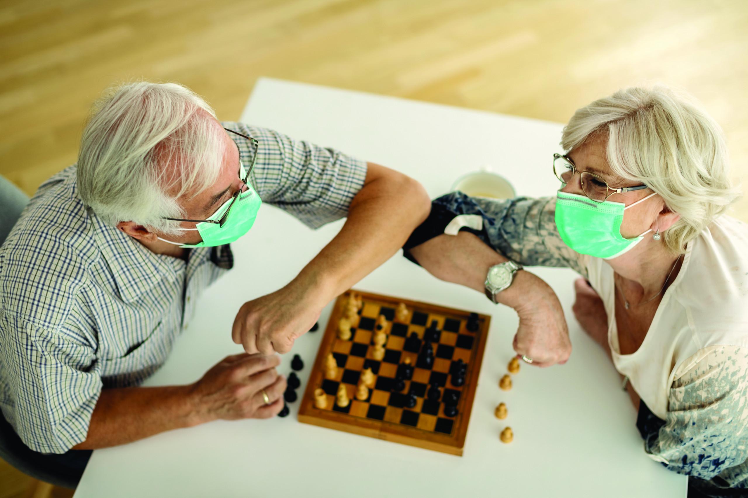 masked elderly couple playing chess