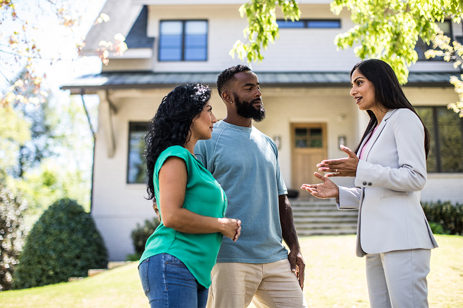 couple with real estate agent in front of house